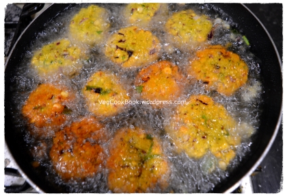 Pan of boiled oil, filled with vada patties for frying
